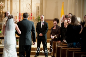 groom-and-family-smiling-as-they-watch-bride-walk-down-wedding-ceremony-aisle-1024x680(pp_w854_h567)